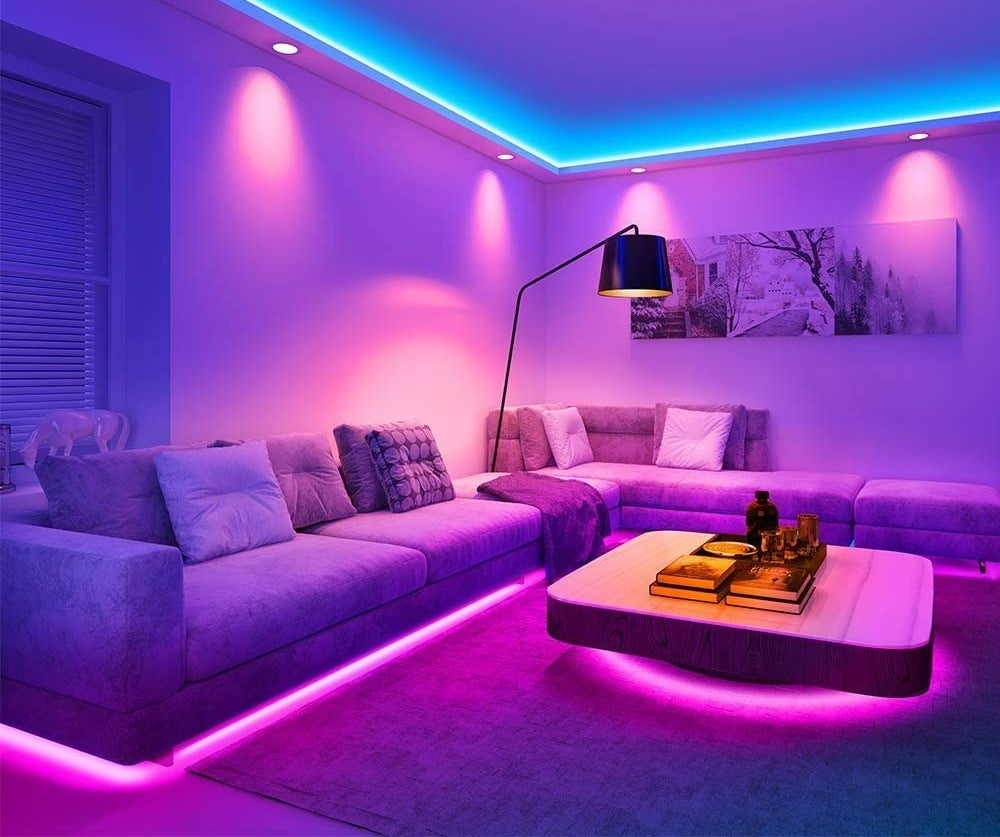 A living room with long couches lined with the LED light strips below them on the floor, and above along the ceiling