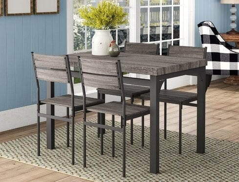 dark brown wood and metal table and four matching chairs