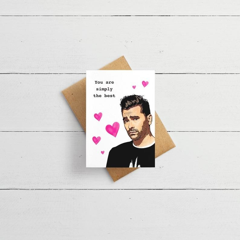 """A white card featuring a drawing of David Rose from """"Schitt's Creek,"""" with pink hearts and the words """"You're simply the best"""" in black type"""