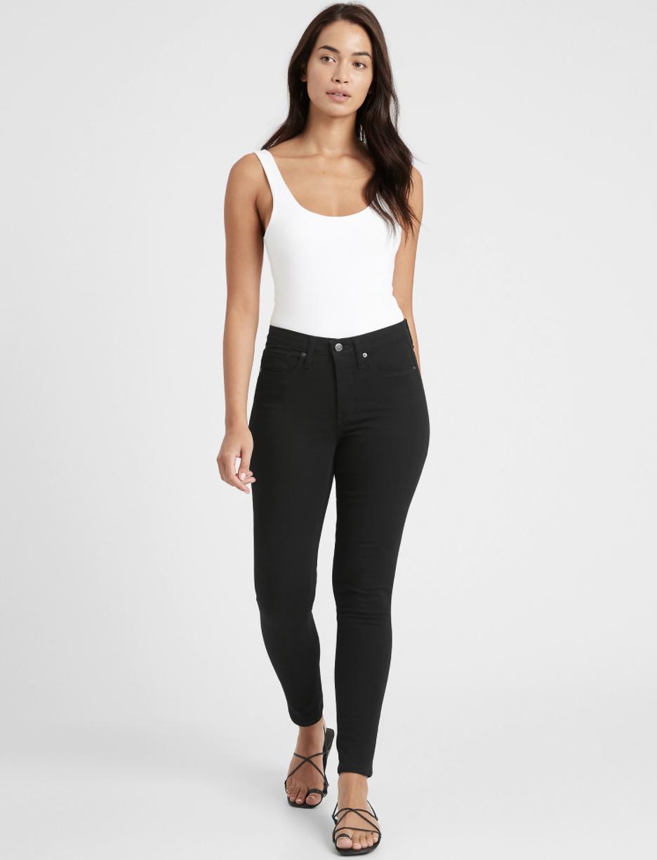 Model wearing black mid-rise skinny fade-resistant jeans