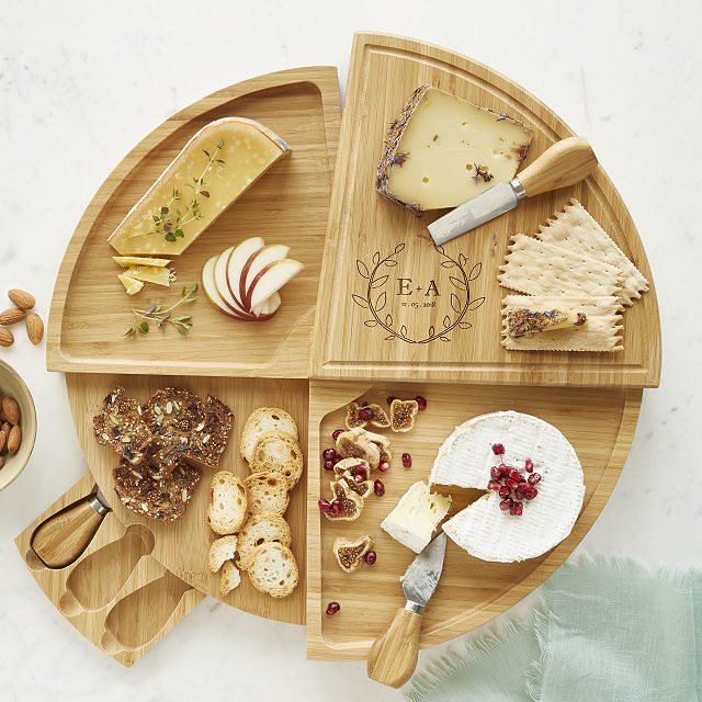 A cheese board with the initials E.A engraved in it with cheeses and crackers on top of it