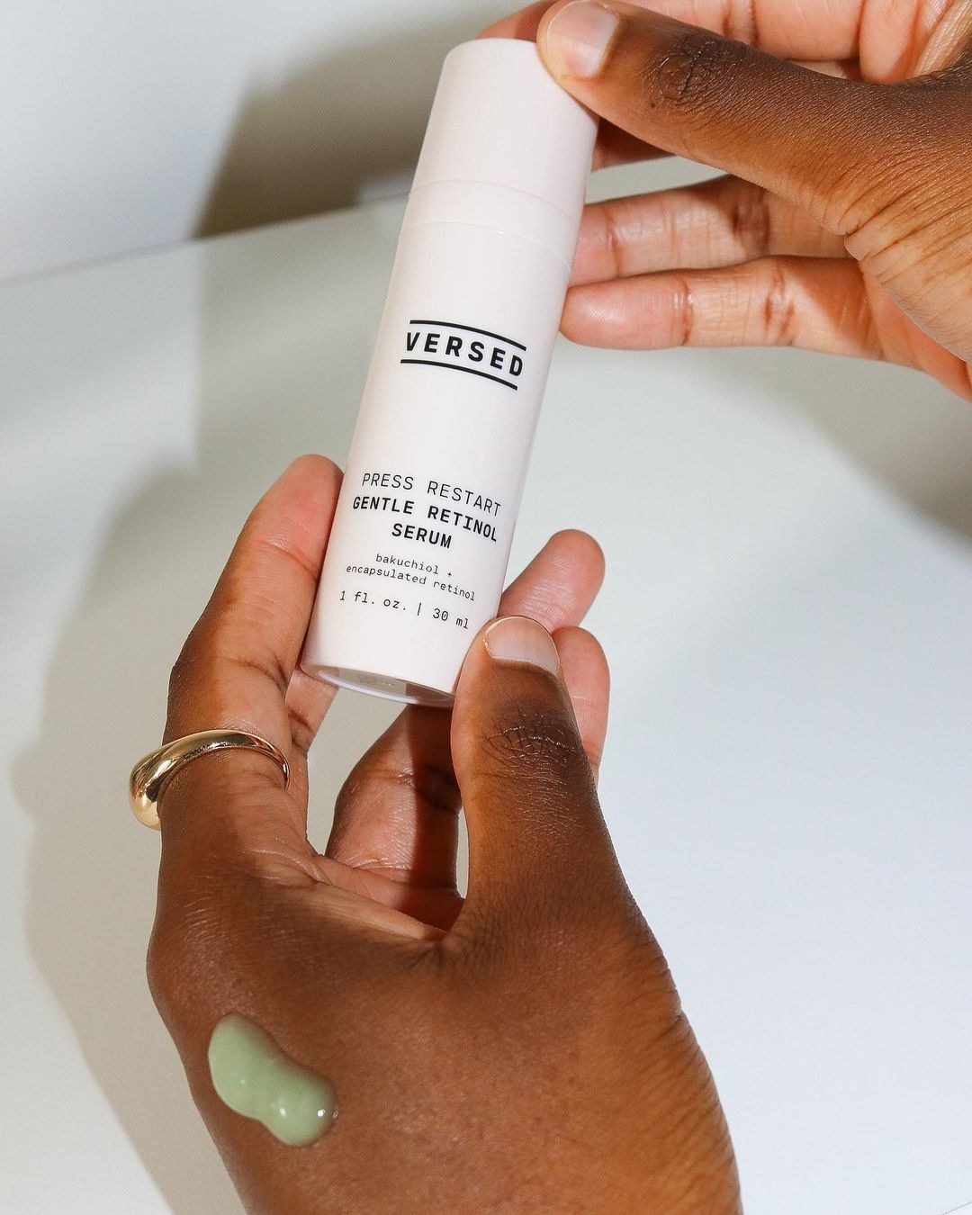 Model with retinol on her hand to show green formula