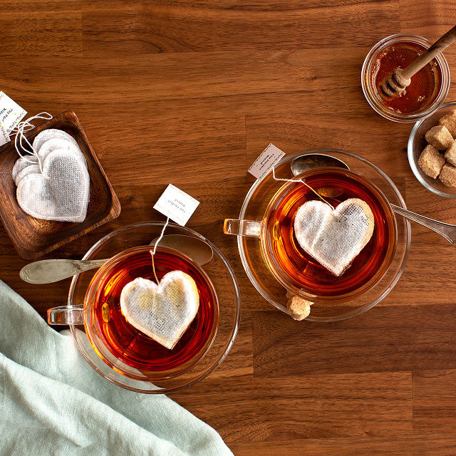 Two heart shaped tea bags inside of two tea cups with a spoon and tea bags next to it