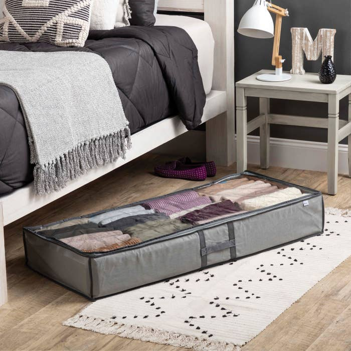 underbed storage bag filled with clothes on a bedroom floor
