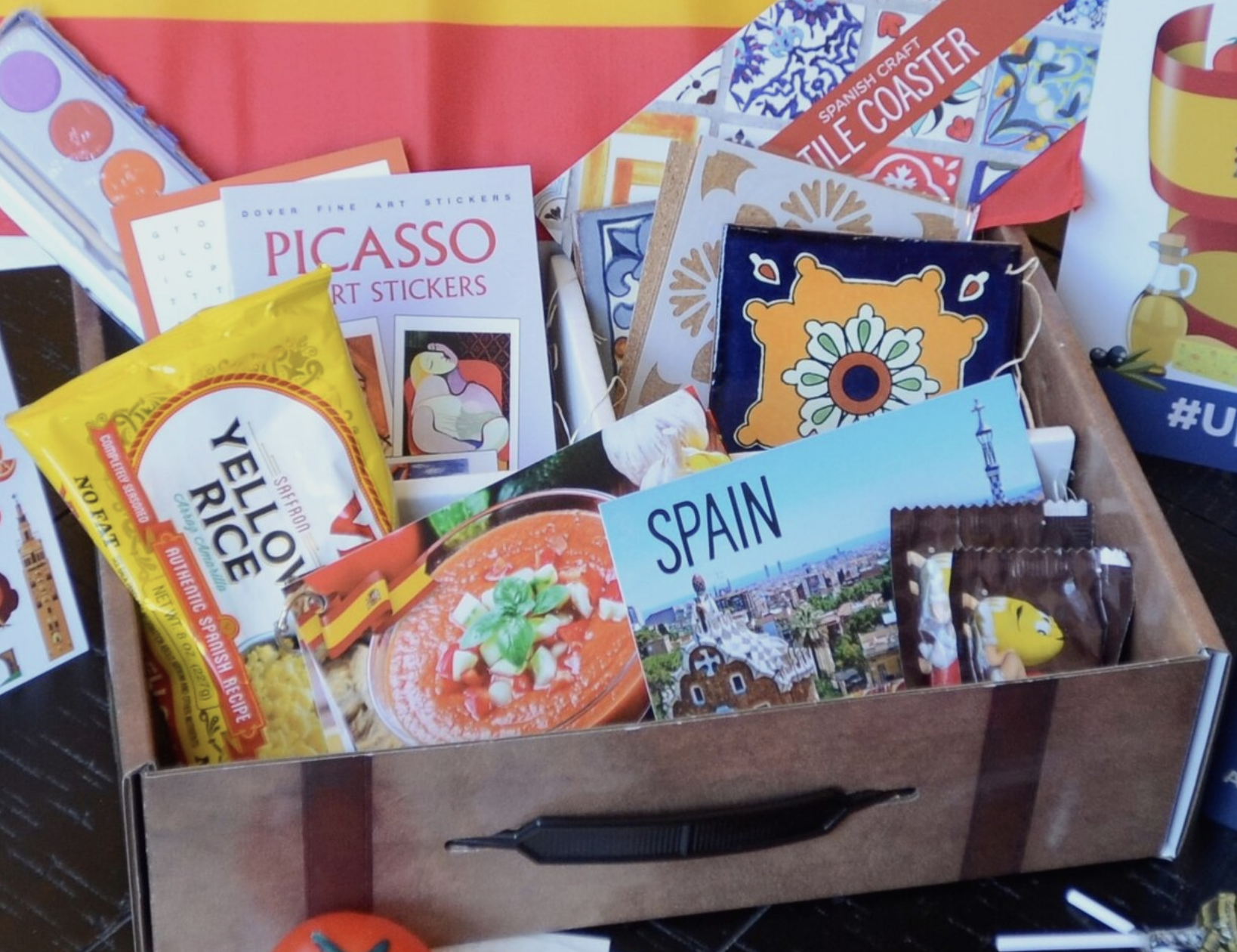 A wooden suitcase-looking box holds a variety of objects from Spain including art, a postcard, yellow rice, m&ms, and a picasso sticker book