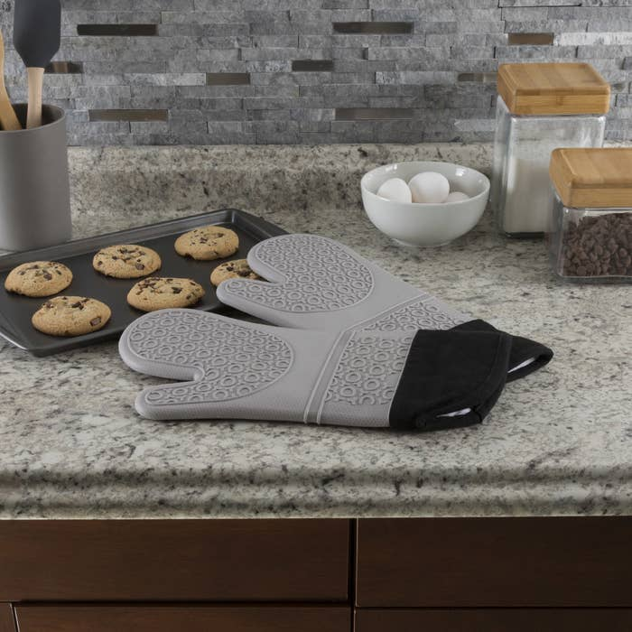two grey silicon oven mitts next to a tray of cookies on counter