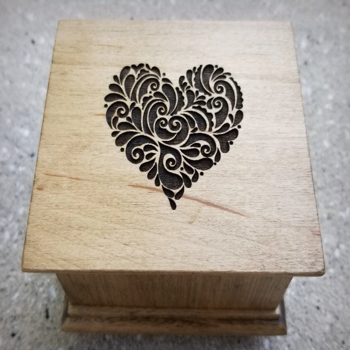 the wooden music box with a carving of a heart on it