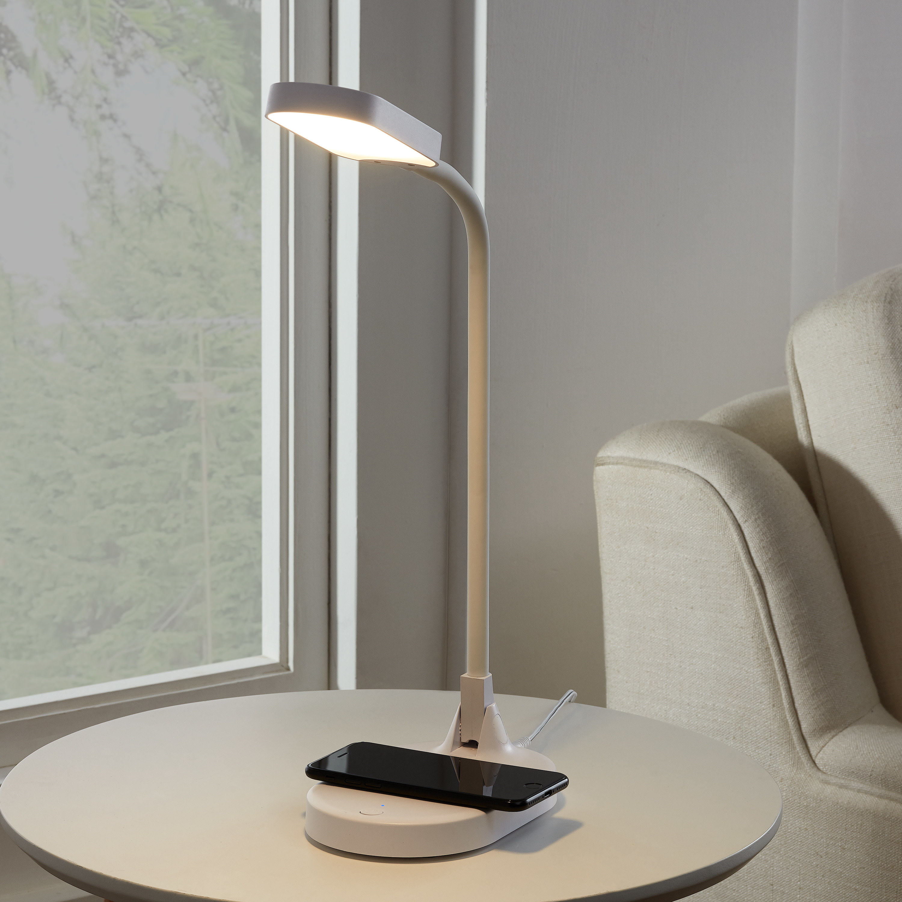 white led charger lamp on side table charging a phone