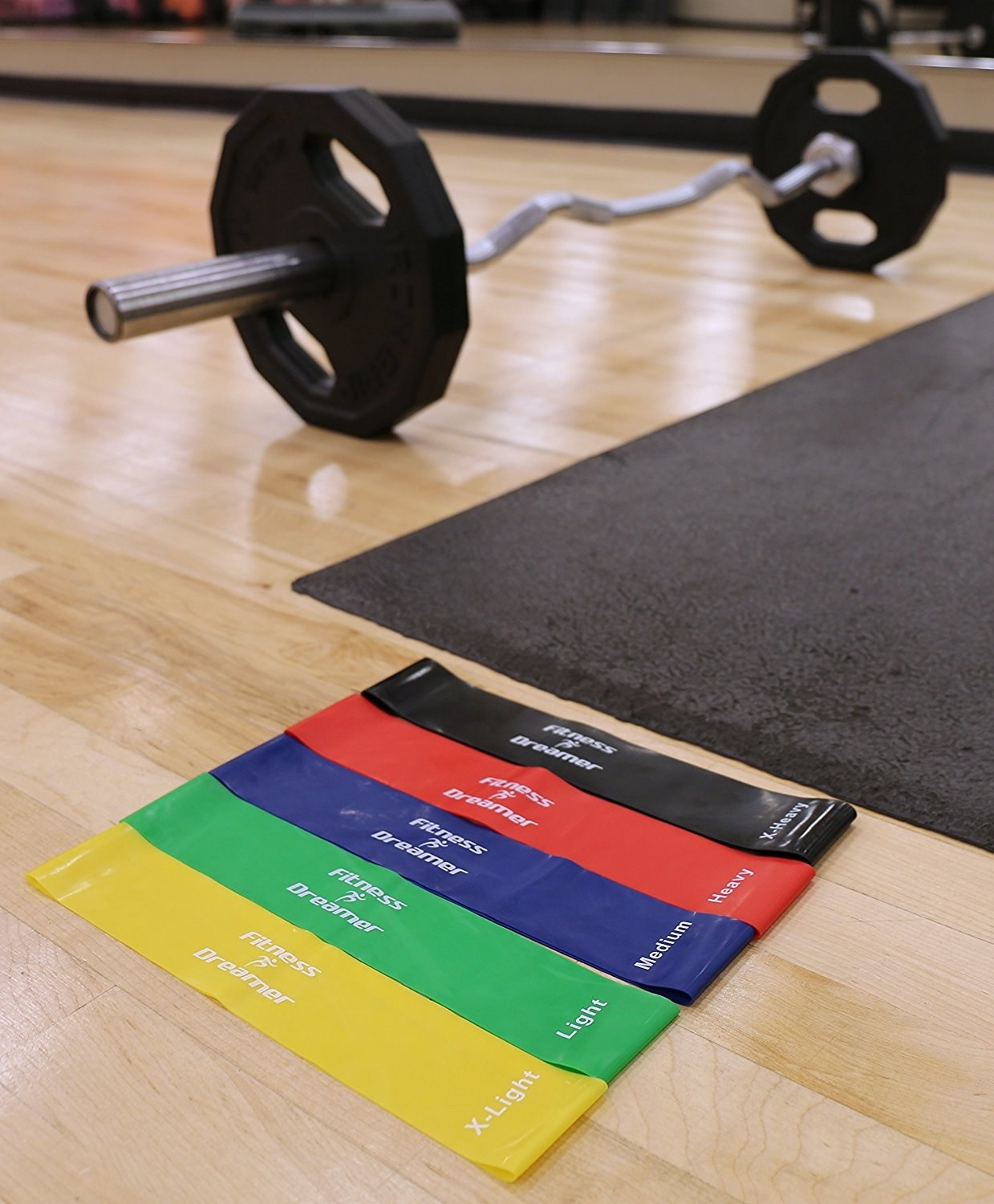 5 different colores resistance bands lying on floor next to barbell