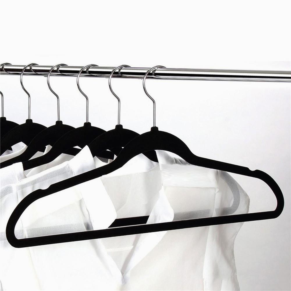 black velvet hangers hanging with white button up shirts  on them