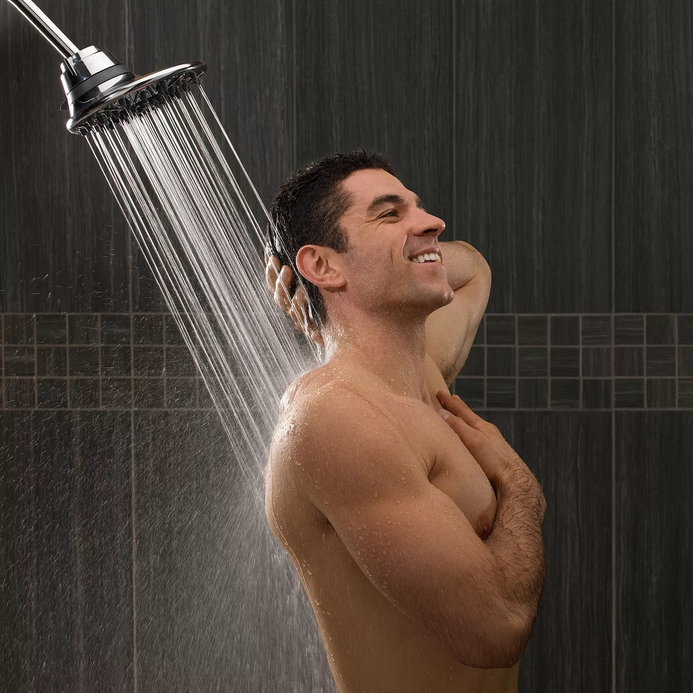 A smiling man showering using showerhead