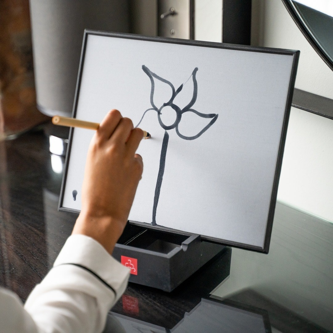 A person painting a flower on their Buddha Board