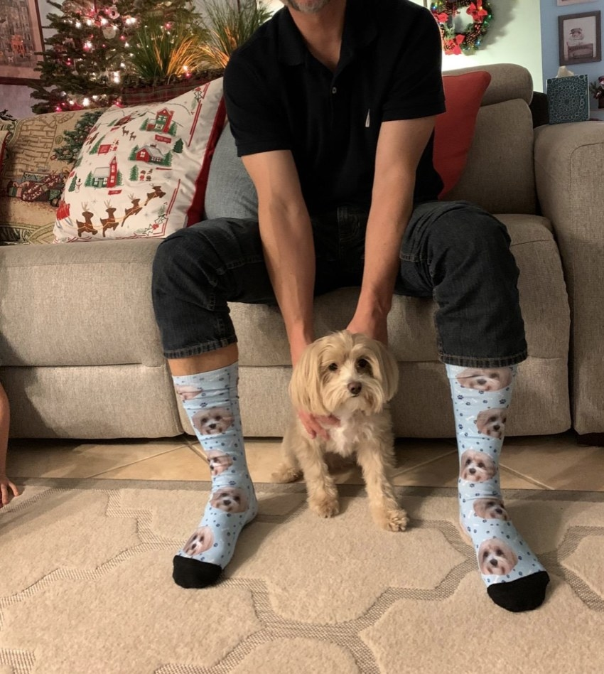 A customer wearing the blue socks while posing with the dog