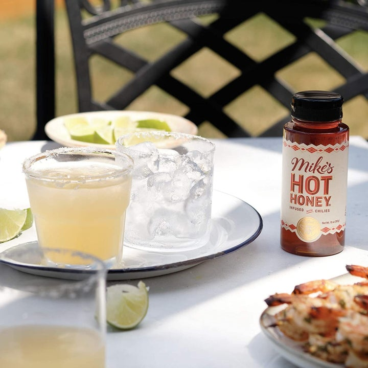 Bottle of hot honey next to cocktails made with it