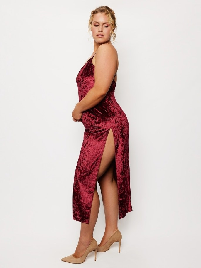 plus size model in red velvet maxi dress with high thigh slit