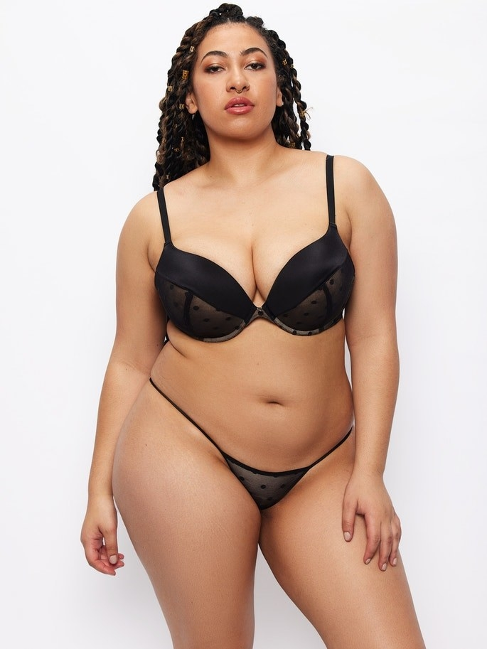 plus-size model with large chest in black full-coverag bra with a plunge fit that helps with coverage