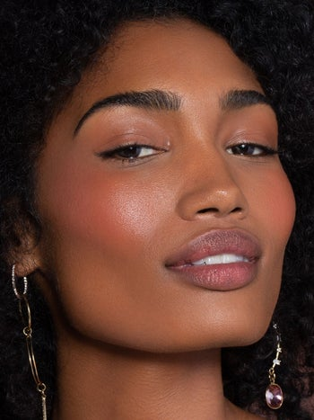 a model with the product on heir cheeks and lips