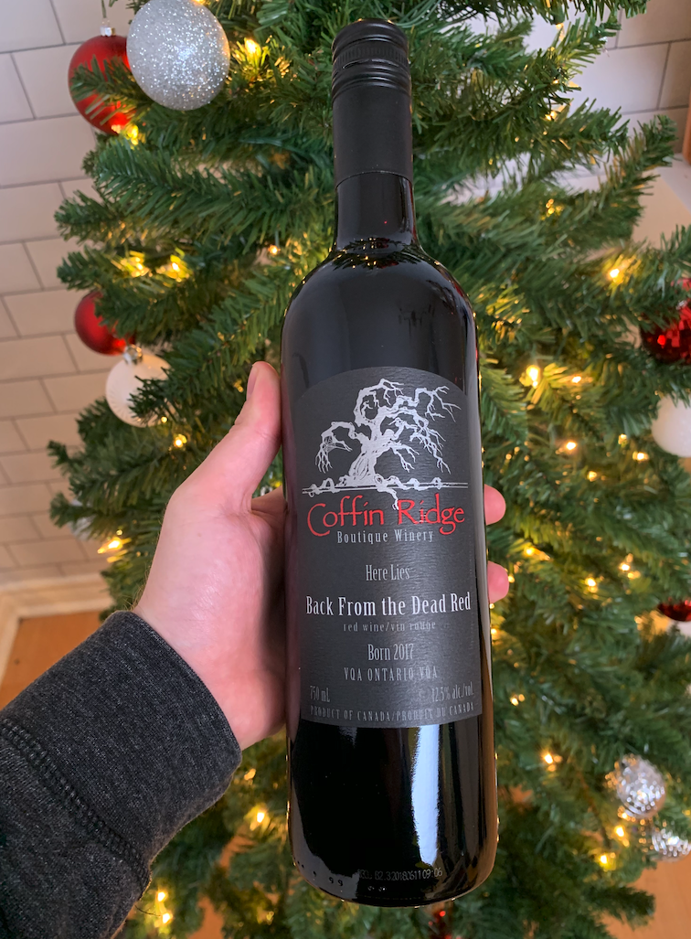 A bottle of  Coffin Ridge red wine in front of a Christmas Tree.