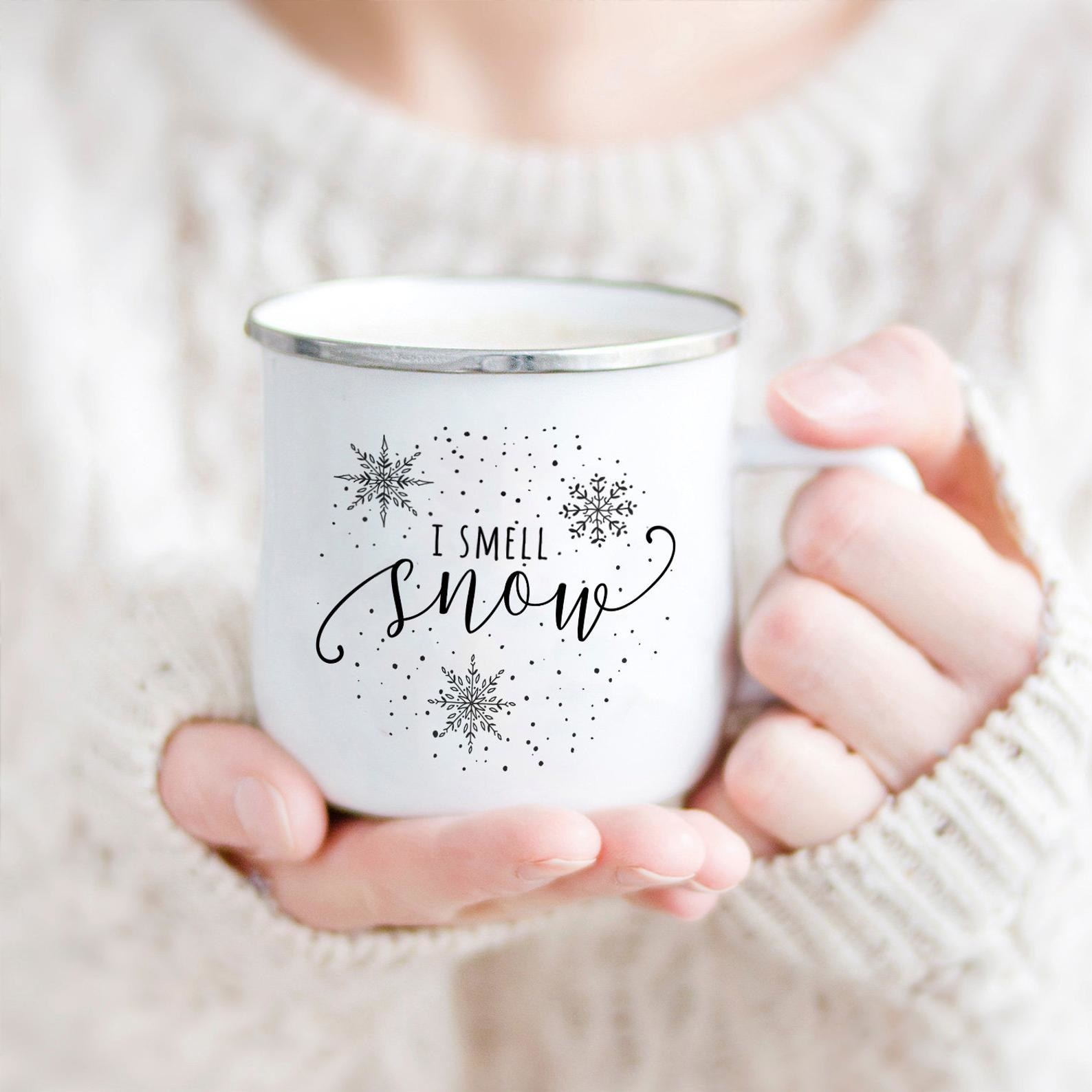 """a model holding a white camp mug with """"i smell snow"""" on it and snowflakes"""