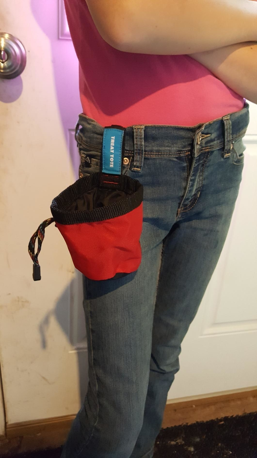 Reviewer's photo of the treat tote attached to their jeans
