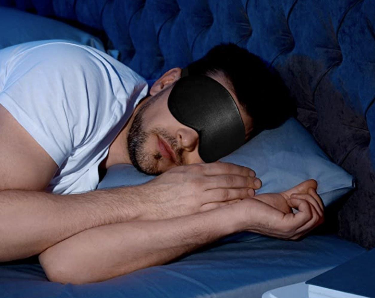 A model wearing the eye mask in black