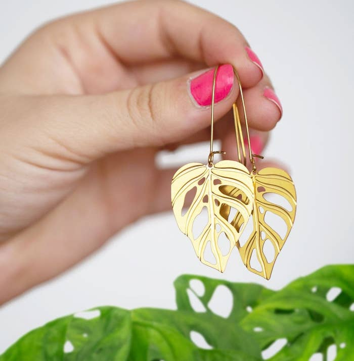 A person holding the monstera earrings above a plant