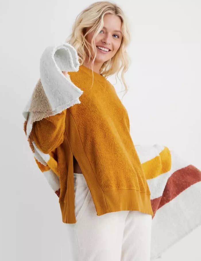 a model in a mustard yellow plush pullover
