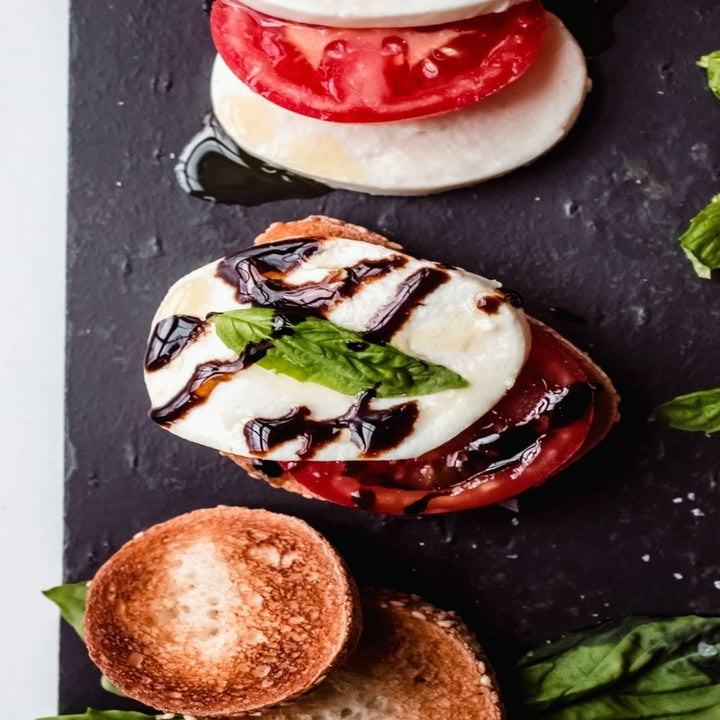 A close-up of sliced mozzarella and tomato on crispy bread with balsamic drizzle and basil.