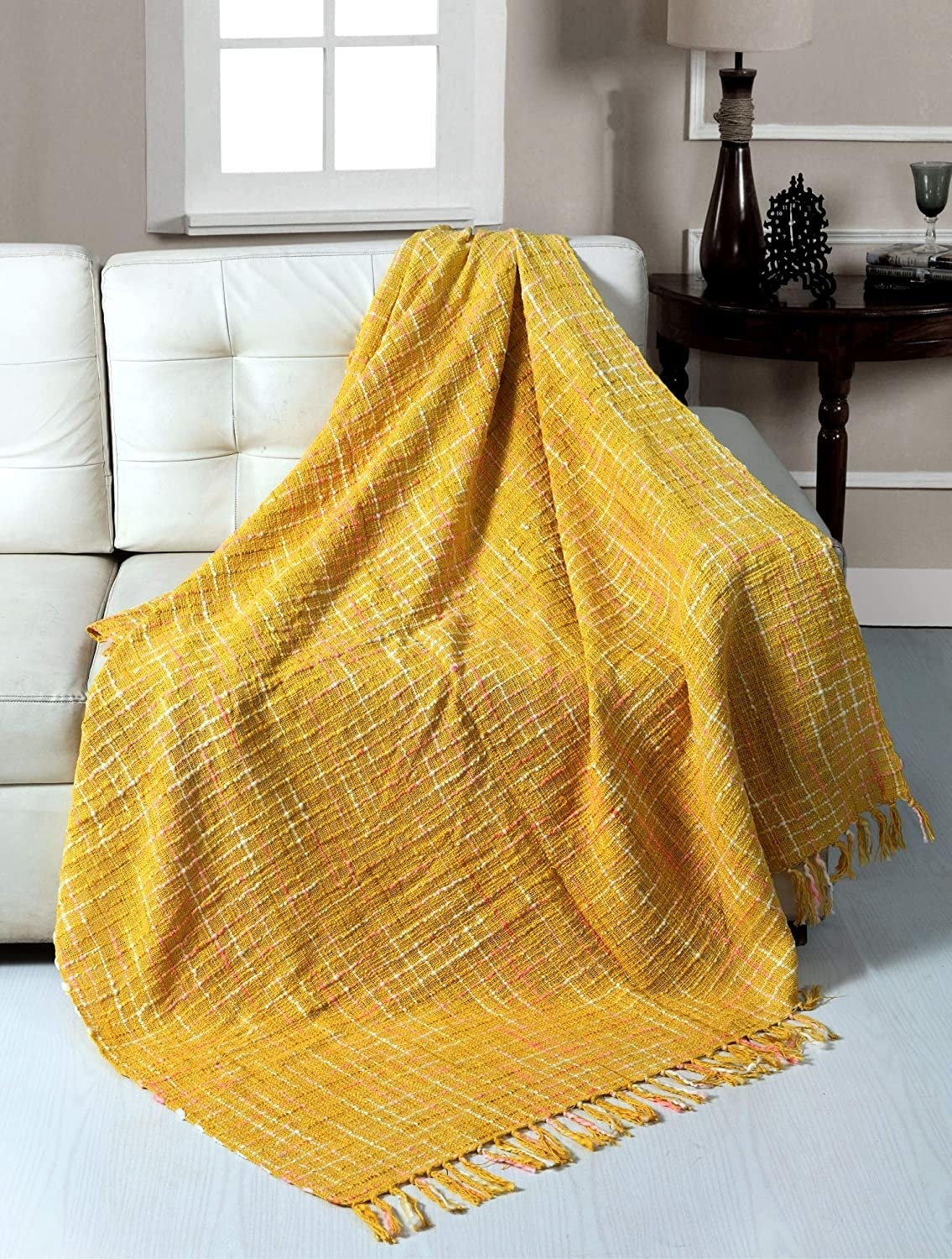 A bright yellow throw blanket draped on an off-white sofa.