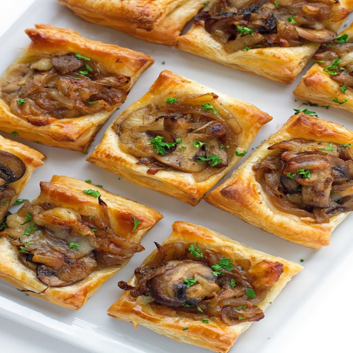 Puff pastry dough bites topped with cheese, mushrooms, and caramelized onions.