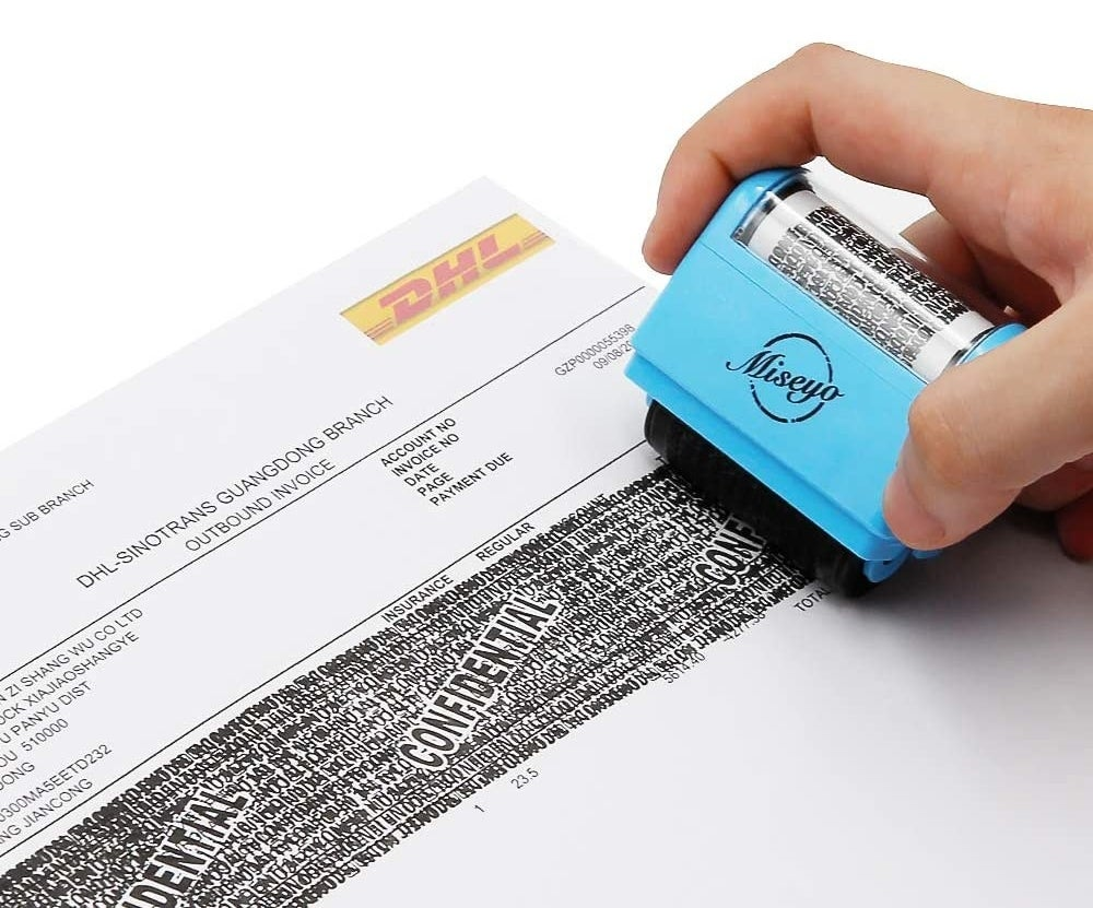 person rolling the stamp across a piece of paper