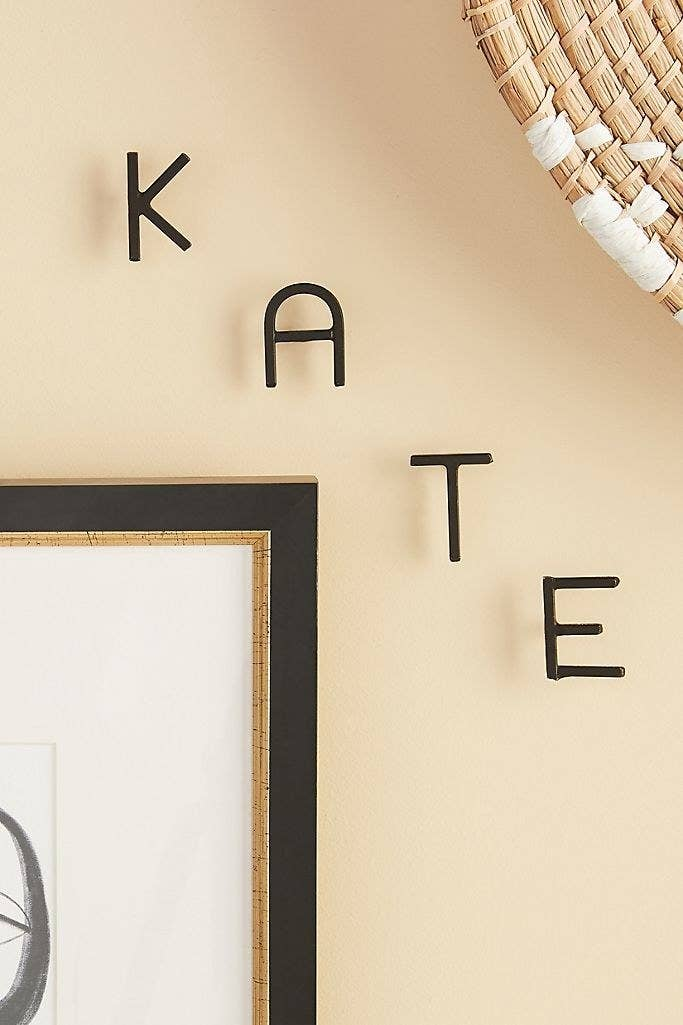 """The nails spelling out """"KATE"""" on a wall"""