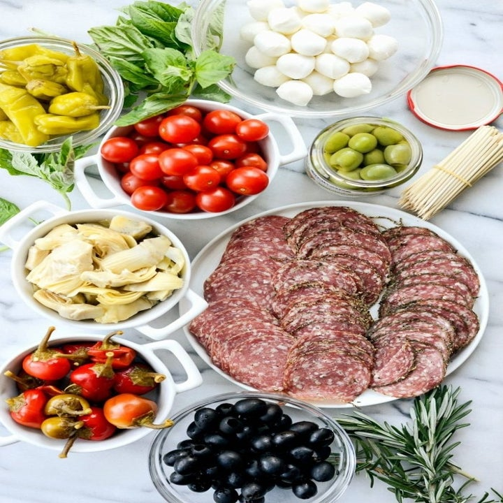 Ingredients for antipasto skewers including salami, artichoke hearts, mozzarella balls, and cherry tomatoes.