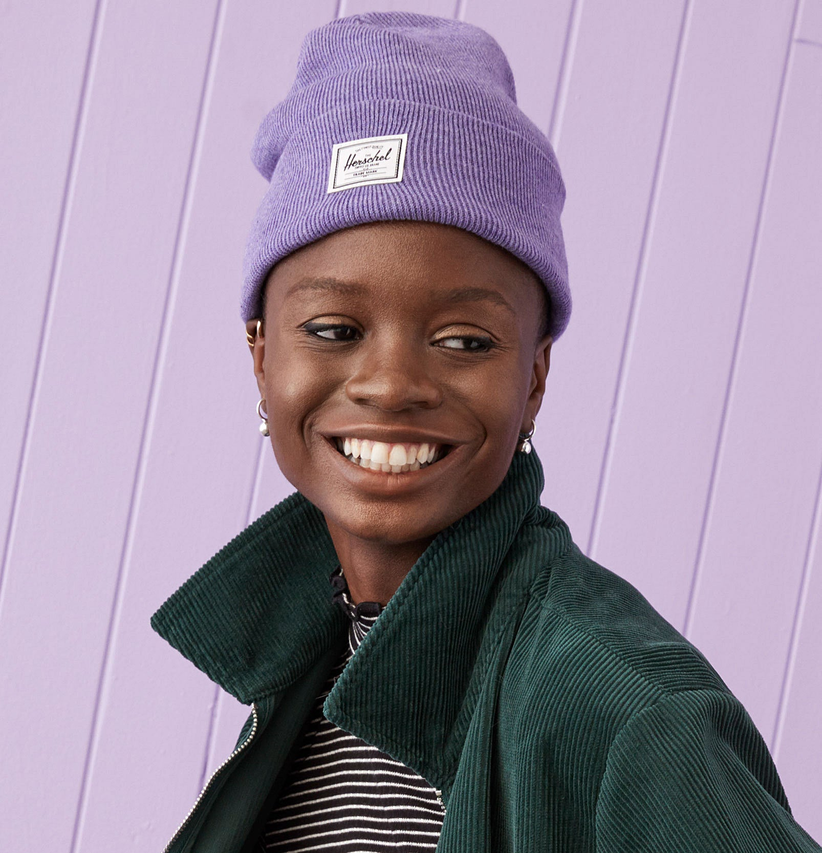 A person wearing the Herschel beanie and smiling