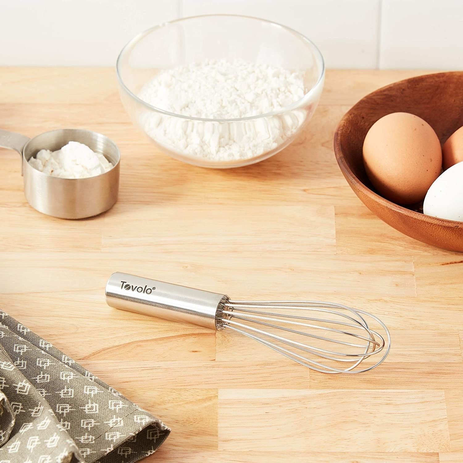 the whisk on a table surrounded by flour and eggs
