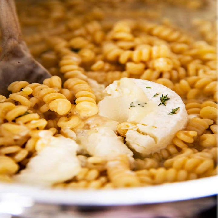 Goat cheese being stirred into a pot of pasta.