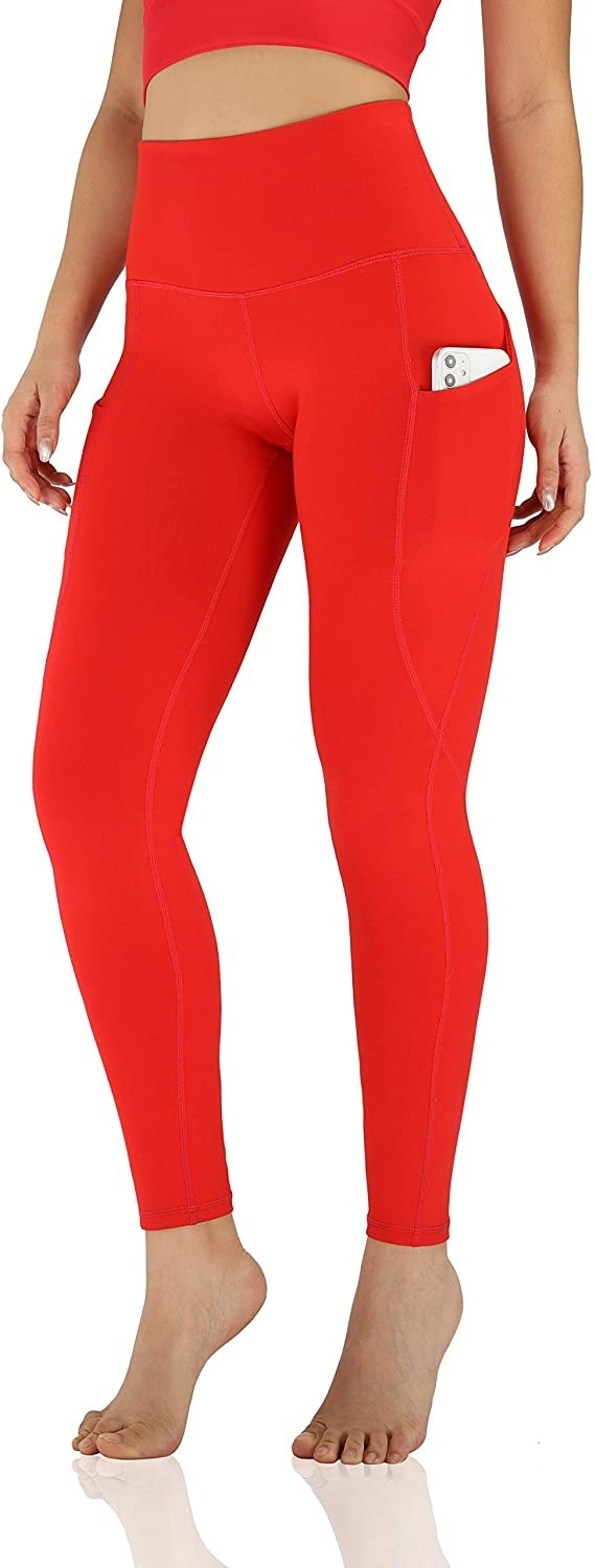A model wearing the red leggings with a phone in the pocket.