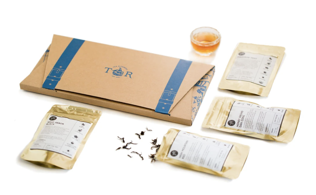 Multiple packs of loose leaf tea sit against a white backdrop with a small glass of amber-colored tea