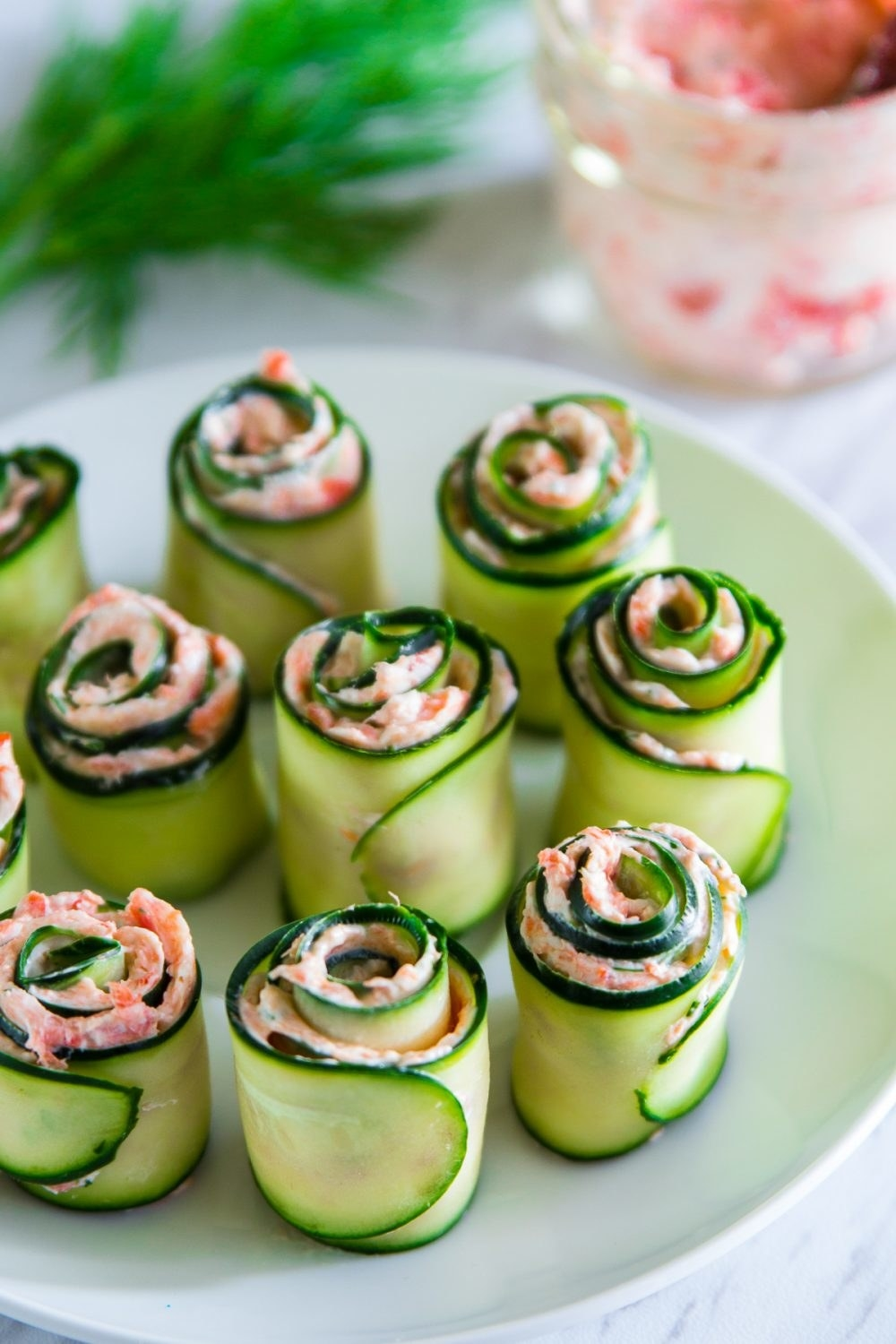 A plate of cucumber roll-ups filled with salmon cream cheese spread.