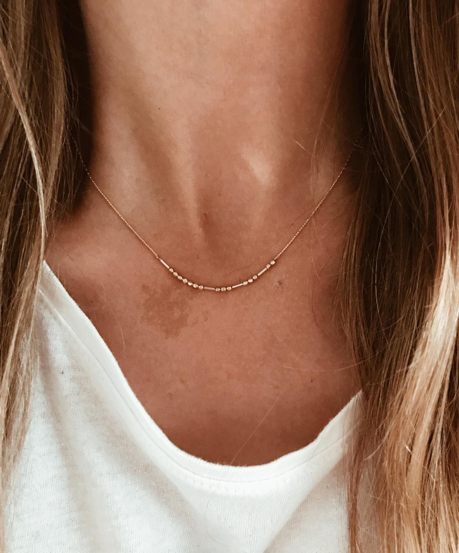 a person wearing the morse code necklace in gold