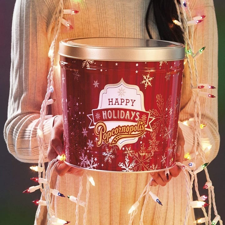 a model holding a red popcorn tin that says happy holidays on it