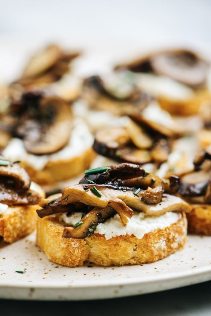 Several crostini topped with creamy ricotta and grilled mushrooms.