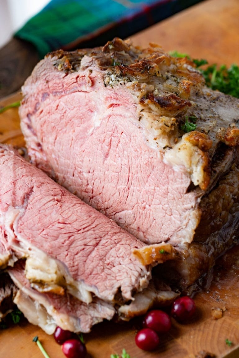 A tender, medium-rare prime rib being sliced to reveal the pink interior.