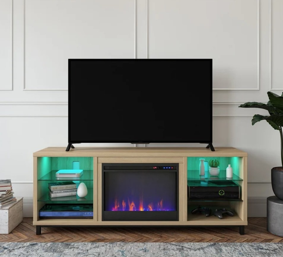 Light wooden TV stand with electric fireplace in the center and shelving units on both sides with LED lights