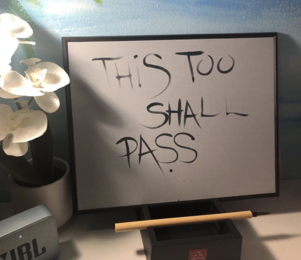 """The Buddha board with the words """"this too shall pass"""" drawn on it"""