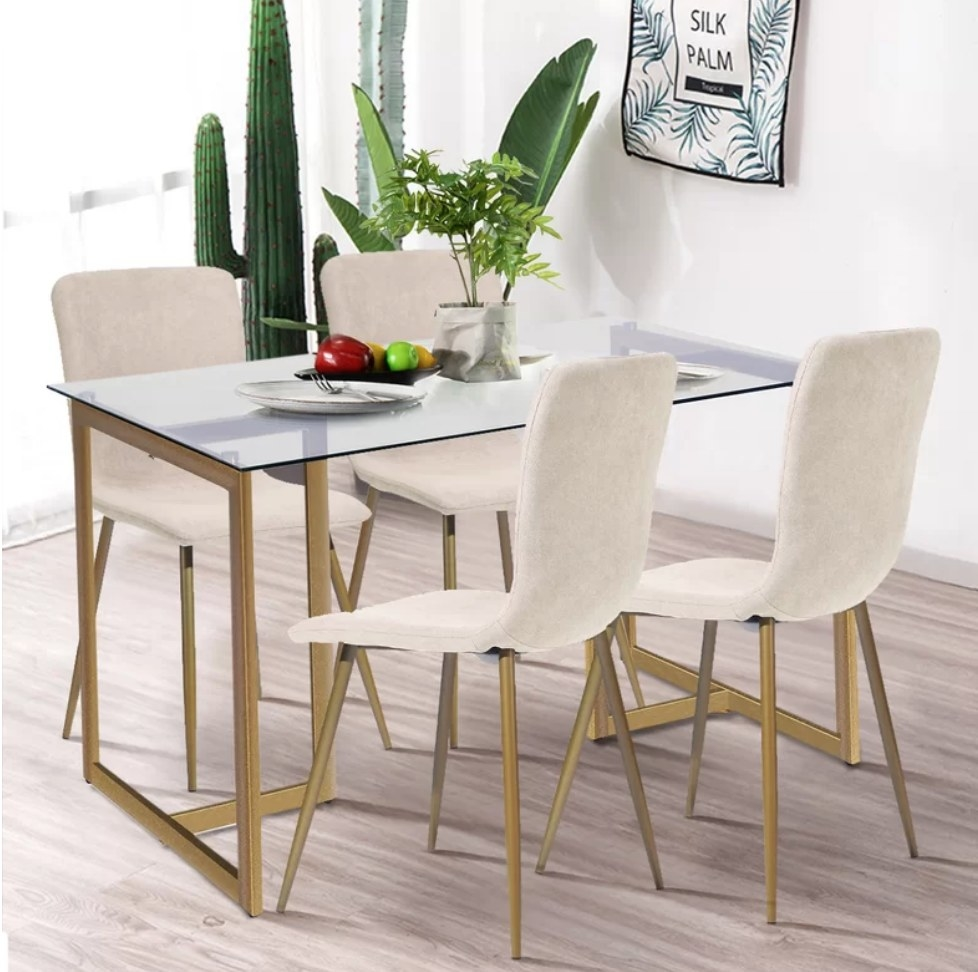 Glass table with bronze legs, four beige fabric chairs with bronze legs