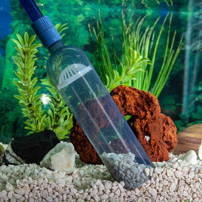 The fish tank vacuum working on tan colored aquarium rocks