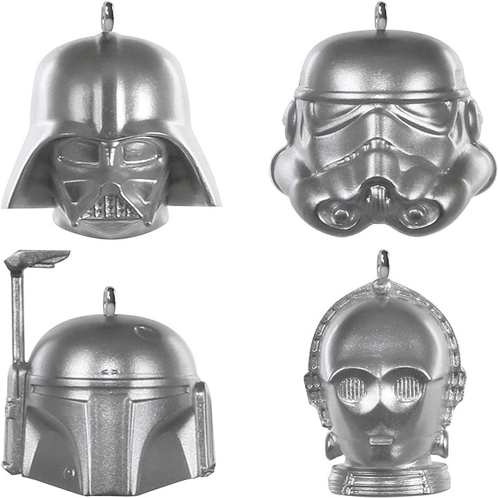 four silver star wars ornaments of darth vader, c3p0, boba fett, and a storm trooper