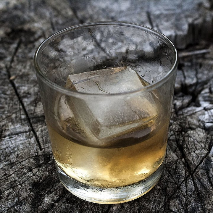 a whiskey glass with an ice cube in it