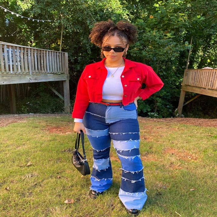Reviewer wearing the flare jeans with patches of different colored blue denim